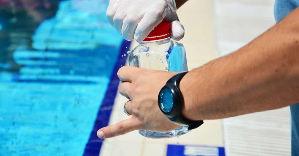 Pool technician taking water from a pool to test PH levels