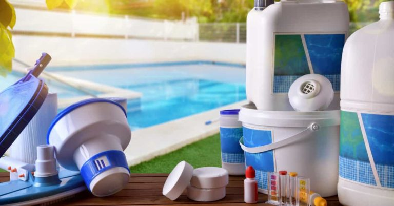 Pool chemicals and filters for a full service job sitting by the poolside