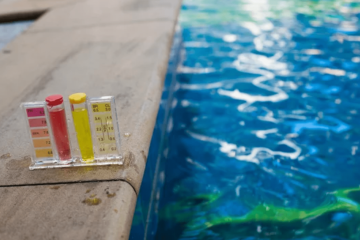 Blue swimming pool with pool testing kit on the edge of pool